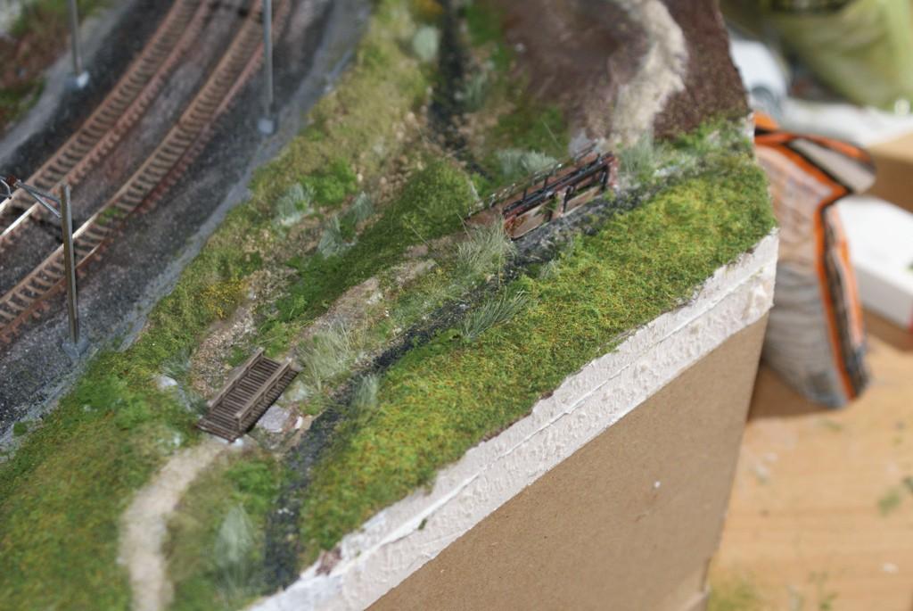 Le sentier passe sur un petit pont en bois au-dessus du déversoir du trop-plein du canal puis sur le petit barrage. Le canal continue vers la droite (hors du module), le ruisseau, la Murg passe par le barrage et longe ensuite la voie.