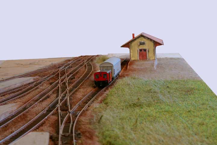 En direction de l'Est, la halle marchandise avec sa place en gravillons, mais séparée de la gare par une zone herbeuse.