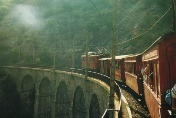 Dans la lumière du soir, le train gagne la vallée et marque un temps d'arrêt pour les photos sur le viaduc des Vaulx.